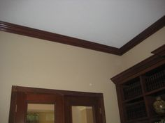 Wooden crown molding and casings both on the ceiling and on the bookcase Crown Molding, Bookcase, Ceiling, Mirror, House, Furniture, Home Decor, Crown Moldings, Homemade Home Decor