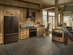 Im so sick of stainless steal, yea its nice but its in EVERY Kitchen! I Love the Bronze! I also Love the wood Color the Floor the beams!