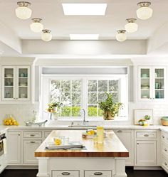 Beautiful all-white kitchen with polished nickel cabinet pills and cup pull hardware.