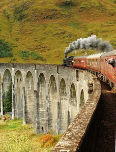 "The ""Hogwarts Express"" crosses the Glenfinnan viaduct (a location made famous in the 'Harry Potter' films), Scotland, UK"