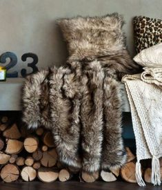 Faux fur + cable knit throw blankets + wood ready to go into the fire.  Doesn't get any cozier than this!