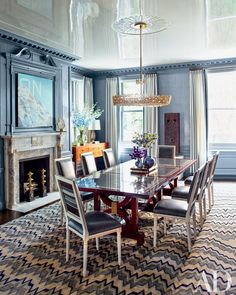 A midcentury chandelier is suspended above the dining room's S. R. Gambrel–designed chairs and églomisé-top table; the painting (left) is by Ed Ruscha | archdigest.com
