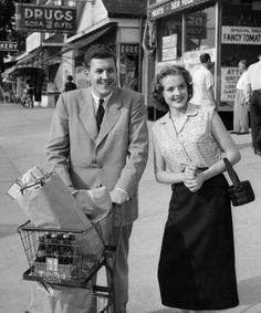 A smiling 1950s couple pushing their cart of groceries out of the supermarket (love her cute little woven handbag!)