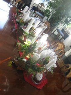 Stunning Christmas table centerpiece with pillar candles and seasonal greens.  www.helenolivia.com