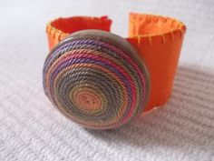 https://www.etsy.com/listing/263687669/adjustable-textile-bracelet-in-orange?ref=shop_home_active_8It is a one of a kind adjustable textile cuff bracelet in orange colour with wooden pendant on it as a decoration. The wooden pendant is decorated with striped thread. The cuff bracelet is covered by an orange silk textile ribbon . The silk ribbon textile is sewed handmade. On the top of the bracelet there is 40 mm wooden jewelry base which is sewed to the silk ribbon.