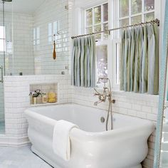Chic bathroom features a wall clad in white beveled subway tiles framing windows dressed n blue and green stripe cafe curtains over a freestanding tub and a wall mount vintage style tub filler next to a corner shower with niche.