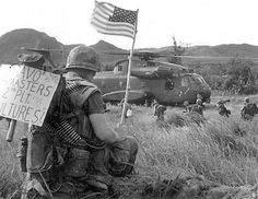 """A Marine from 2nd Platoon """"Vultures,"""" of Bravo Company """"Bushmasters,"""" bares the Stars and Stripes while others from his unit board a CH-53A Sea Stallion with Marine Heavy Helicopter Squadron 463 in Vietnam in 1967."""