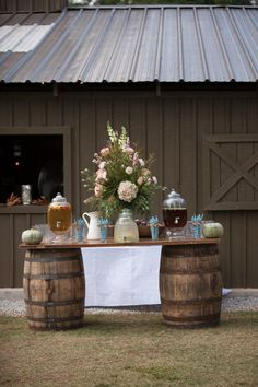 This beautiful fall wedding took place at Vinewood Plantation, a historic Georgia barn wedding venue and plantation house dating back to 1852. A charming venue, Taylor and Ryan exchanged vows under an ancient pecan tree with the reception following in the barn. Although the timbers of the barn were already decorated with cafe lights and chandeliers, we love the added touch of hanging small jars of flowers. Light green heritage pumpkins added to the lovely platte of green, white and pink…