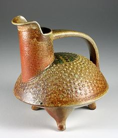 This piece is mostly hand built and was made in 2005. It is one in a series of pieces inspired by Neolithic Chinese forms from about 4,000 years ago. It has a thin wash of a shino type glaze, with some small dots of a chrome green glaze. It stands about 21 cm tall. Pouring vessel by Steve Irvine.