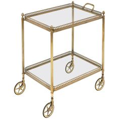 In the style of Maison Baguès, this stunning bar cart from the 1940s is made of beautiful gilt brass, with two glass shelves surrounded by gilt brass galleries. The flawless details and craftsmanship make this a wonderful addition for cocktail hours!