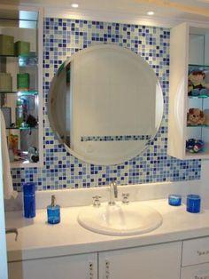 As pastilhas de vidro em azul e branco combinadas com o espelho redondo e com os nichos laterais brancos – que tem prateleiras de vidro – dão o charme deste banheiro assinado por Lívia Gobetti. A bancada tem um tampo de mármore branco. A iluminação é feita através de lâmpadas dicróica.