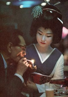 Geisha presents a light to a diner in a Tokyo restaurant, 1969