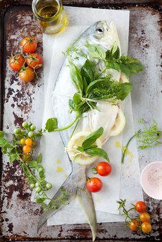 Fresh whole fish on a plank, basil, cherry tomatoes, herbs, olive oil