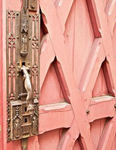 I love the whole look... the baroque detailing of the handle / lock and the countryish geometric door!
