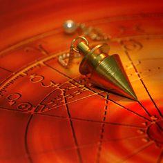Gold pendulum lying on a beautiful orange background ,Magic pendulum. Gold pendulum lying on a beautiful orange background ,