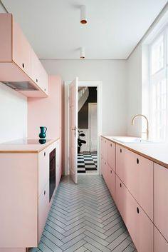 Cozinha com armários rosa millennial e puxador do tipo cava perfurado na madeira, metais dourados.