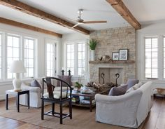 great windows, doors, beams, stone fireplace, rustic wood - Beach Style Living Room by Wettling Architects