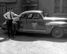 """Our Flashback Friday Photo is from August 1944 and shows then Patrolman Lester Powell with Radio Car #2 in front of the town garage. The building previously housed the police department and was known as the """"Bastille."""" Powell went on to become Chief of Police in 1955 and retired in 1967."""