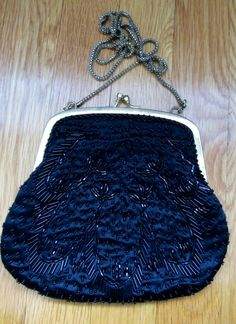 Beautiful little hand-beaded (in China) La Regale Ltd vintage evening bag. Black satin covered in a beautiful art deco floral pattern of hand-stitched black seed beads. The round beads are glossy and the tubular beads have a metallic/iridescent sheen. The back-side of the bag has less detail than the front.  The bag is suspended from a gold chain, which can be tucked away to convert to bag to a clutch. There is a snap closure which is gold tone, along with the metal frame (and chain). Th...