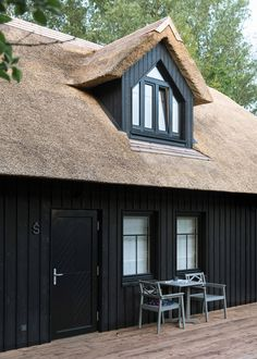 After finding the remains of a fishing hut that had burnt down on the site, the Svencioneliai-based firm drew on its traditional form for the new design, which features a thatched mansard roof and charred timber cladding in reference to the fate of the old building. Condominium Interior, Cosy Apartment, Wood Plank Walls, Mansard Roof, Porch Area, Contemporary Building, Best Architects, Dormer Windows, Wooden Staircases