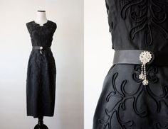 Classic and chic vintage 1940's black cocktail dress with a feminine shape. Subtle art deco cutout neckline and intricate organic patterned detailing. Comes with a matching belt with a rhinestone clasp.