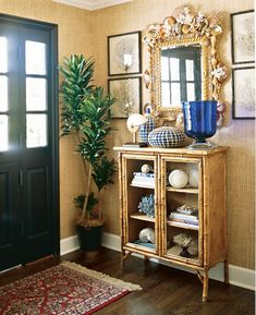 An antique English bamboo cabinet introduces the British Colonial style in the entry. Seashells, coral, and a shell-encrusted mirror reference the seaside location.