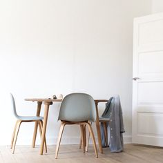 Spisebord fra Designer Zoo med hvid bord hvid plade og ben i egetræ. Stole fra Gubi med egetræsben og sæde Nightfall Blue