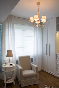 Poltrona de amamentação branca com mesinha e abajur, lustre.