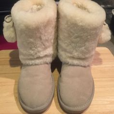 Rjs pomp pomp sheepskin boots Gently worn. Some darkening in fur on left side shoe possibly from storage. Not as noticeable in person as it is in picture. Just like uggs. Super cute.  Im a size 7 regularly and they fit me UGG Shoes Winter & Rain Boots