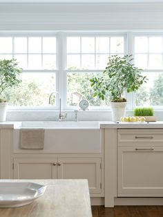windows (sash), simple cabinets w/legs, sink, counters, counters continue up backsplash to window