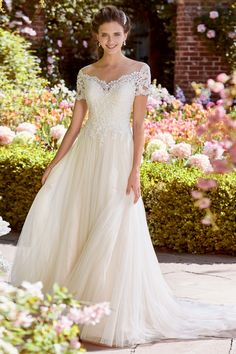This A-line gown from Rebecca Ingram features an off-the-shoulder neckline, lace bodice, short sleeves, and a tulle skirt.