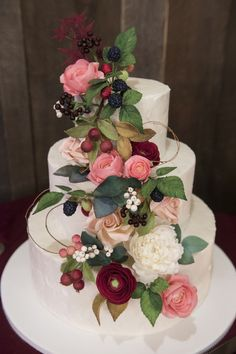 The couple had a beautiful three-tiered cake with a cascade of flowers and berries. Reception Venue: The Woodlands at Cottonwood Canyon Floral Design: Budget Bouquet Cake: Cabin Ridge
