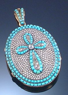 TURQUOISE, HALF SEED PEARL AND DIAMOND LOCKET, MID 19TH CENTURY The oval locket designed with a raised Latin cross motif to the centre composed of calibré-cut turquoise and rose-cut diamonds, on a background of half-seed pearls, to an outer border and surmount set with calibré-cut turquoise, opening to reveal and glazed compartment, the reverse engraved with foliate scroll motifs, French marks to bale.