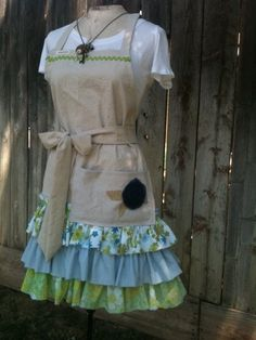 Washed Dropcloth with three layers of mismatched vintage fabrics in Beachy greens and blues. A tulle rose in Navy Blue embellishes the drop cloth pocket and the bib is topped by bright green rick rack. by Shabbycowgirl