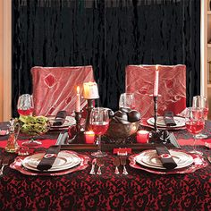 "Love this table setting - ghoulish but classy too, just like vampires! cheesecloth ""webs"" on chairs, crepe paper drapes, red under the black lace table cloth, even white candles with red dripping down. Excellent. . ."