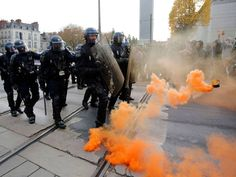 """22 November 2014 A smoke safety flare floats in the air near French riot police at a protest demonstration against """"police brutality"""" in Nantes, western France. People protest against the use of force by police and in memory of 21-year-old environmentalist Remi Fraisse who died during a violent stand-off over the weekend October 25-26 between police and ecology protesters seeking to prevent construction of a dam in Sivens REUTERS/Stephane Mahe"""