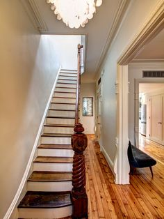 In this first-floor-entry hallway that opens up the house from front to back, a carved newel post anchors the staircase with hardwood floors that have been refinished, making the space shine.