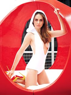 Alison Brie plunging one piece and sky high yellow Louboutins
