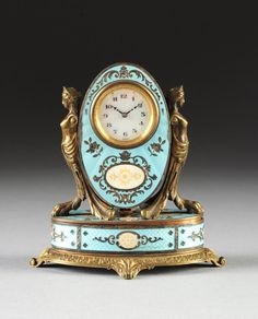 """A MINIATURE AUSTRIAN BLUE GUILLOCHÉ ENAMEL CLOCK, EARLY 20TH CENTURY,  the circular white enameled Swiss dial with Arabic black hour chapters alternating gilt dot minute marks surmounted by initials """"R A"""", within an oval pale blue guilloché swiveling case centering various engraved line patterns and silver plated floral stems above a conforming radiating ivory colored reserve of gilt details reversing to a mirrored panel, flanked by scrolling bronze caryatid supports ending in paw feet, on a…"""