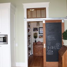 A sliding barn door with a chalkboard inset separates this kitchen from the famiy room. | thisoldhouse.com/yourTOH