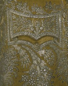Detail, man's coat, France, 1780s; silk velvet, silver spangles  thread, glass paste. Sprays of flowers embroidered with paste, silver spangles and purl decorate the pocket and hem of this velvet coat...The pastes on this coat have clouded and the silver backing tarnished, but when new they would have sparkled like diamonds. Once a bright turquoise, the dye colouring the silk velvet has faded, giving the coat a greenish hue.