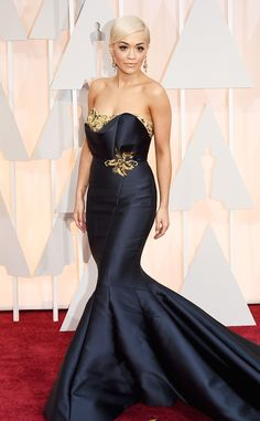 2015 Oscars: Red Carpet Arrivals - Rita Ora attends Academy Awards ceremony in a beautiful dark colored gown designed by Marchesa
