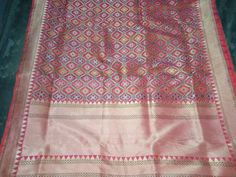 This pink saree with its closely woven geometric multicolored flowers in a lattice is framed by a zari border with a ribbon of pink running on the edge. A plain pink blouse completes this handwoven Banarasi.