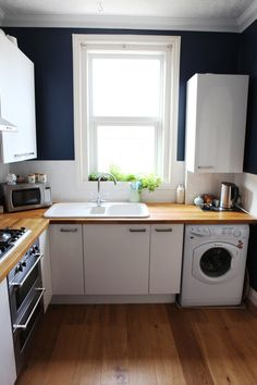 Charlie's Charming Townhouse; Kitchen walls: Stiffkey Blue by Farrow and Ball; see the off-center sink and off-center space between cabinets and window - it works.