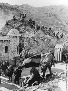 Spanish National troops sit on a rocky hillside at the French border post of Port Bou Cerbere. (Photo by Three Lions/Getty Images). Circa 1936