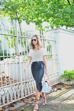 Look da Helena Lunardelli com saia lápis de couro e camiseta básica branca. Detalhe para os acessórios –óculos de sol e bolsa divertida e colorida.