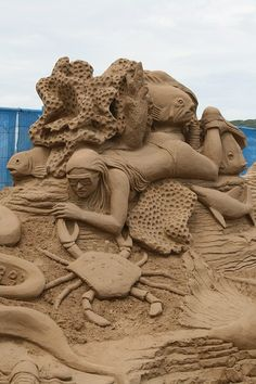 Sand sculpture: woman in bikini and goggles swimming amongst sea life ... fish, coral, crab #sand #ocean #art