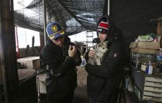 In this Friday, Feb. 23, 2018, photo, American freestyle skier Gus Kenworthy, left, and his boyfriend Matthew Wilkas hold dogs at a dog meat farm in Siheung, South Korea. Kenworthy saved five stray dogs during the Sochi Olympics four years ago and is considering adopting one of the many puppies he met Friday after finishing competition the Pyeongchang Games.