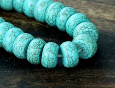Magnesite Rondelles - White magnesite is dyed blue and crazed with heat and black or brown dye to look like turquoise with matrix.. If honestly represented as it is here, it makes a good looking turquoise substitute.