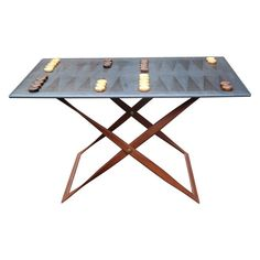 An artizan made luxury backgammon table of forged steel construction. Entirely covered in saddle hide, the top being uniquely hand coloured and stitched in England.The table is adjustable in height and reversible.The counters are rare vintage bakelite circa 1940's and is adjustable in height and is reversible.The table owes much to the influence of Adnet and Hermes and is designed by Nick Plant, who has been producing leather furniture since 1990. A truly unique piece and variations can ...